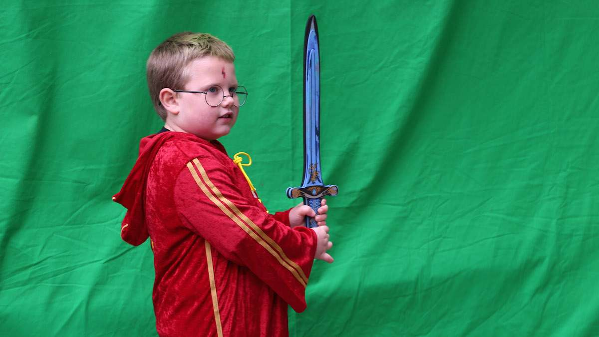 Jamison Walsh, 6 poses in front of the green screen with his magic sword (Natavan Werbock/for NewsWorks)