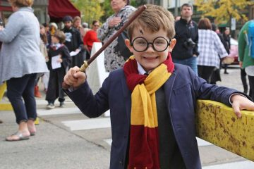 First grader David waving his magic wand at the Harry Potter Festival in Chestnut Hill, in 2015. (Natavan Werbock for WHYY)