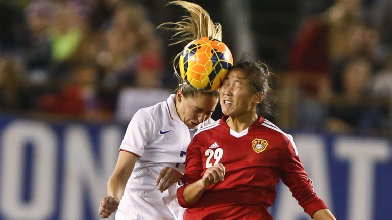 China forward Yang Li and U.S. midfielder Morgan Brian vie for a head ball. (Lenny Ignelzi/AP)