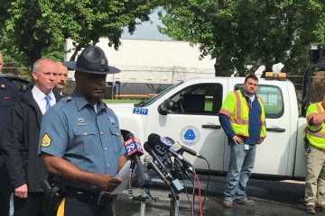Delaware State Police Master Cpl. Jeffrey Hale details the fatal crash near the scene of the incident on Quigley Blvd. in New Castle Thursday afternoon. (Nichelle Polston/WHYY)