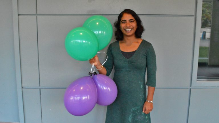 Franklin Institute chief bioscientist Jayatri Das  holds green balloons full of helium, and purple balloons full of sulfur hexaflouride. (Paige Pfleger/WHYY)