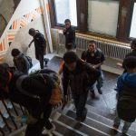Students pass though a stairwell at Overbrook High School. The school has 5 floors, only 3 of which are in active use, not incuding the basement levels. (Emily Cohen for NewsWorks)