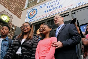 Hill-Freedman Principal Anthony Majewski poses with students (from left) Jason Temple, Serenity Stephens and Destinaé Mason before the ribbon is cut for the school's new 9th grade class. (Emma Lee/for NewsWorks)