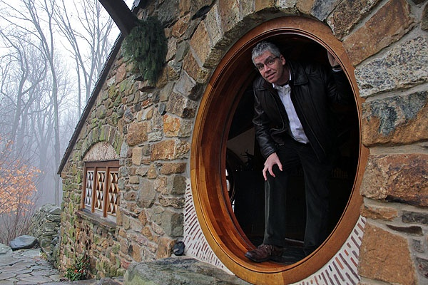 <p>Architect Peter Archer, who designed Vince Donovan's hobbit house emerges from the round door that barely accomodates his 6-foot height. (Emma Lee/for NewsWorks)</p>