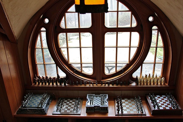 <p>A collection of Middle Earth themed chess sets are on display before the round butterfly window in Vince Donovan's hobbit house in rural Chester County. (Emma Lee/for NewsWorks)</p>
