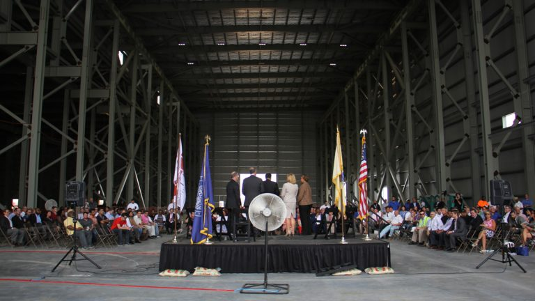 Government officials attend a ceremony for the raising of the final steel beam at Holtec International. The company got $260 million in tax incentives to build its manufacturing plant in Camden. (Emma Lee/WHYY)