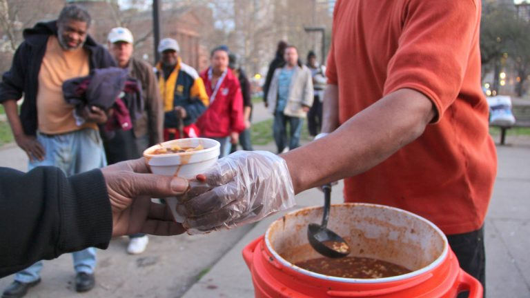 Homeless and hungry people line up for a meal near Logan Circle across from the Family Court building on Vine Street. (Emma Lee/WHYY file)