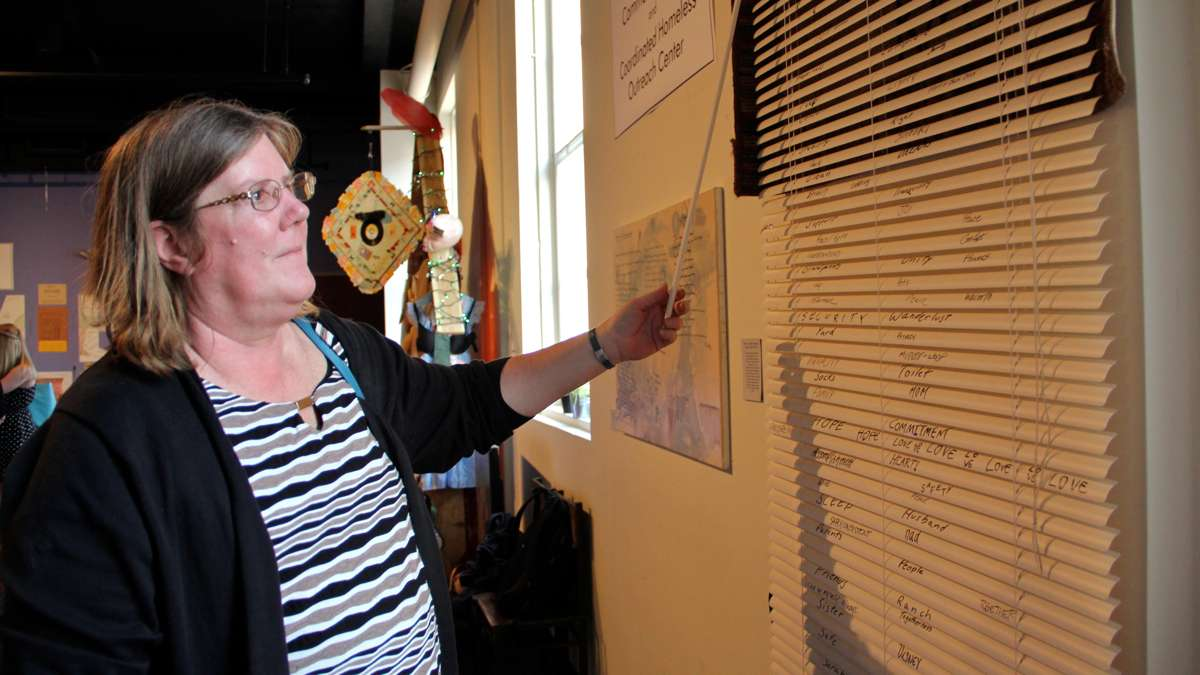 Genny O'Donnell, director of the Coordinated Homeless Outreach Center, looks at an art installation at Theatre Horizon in Norristown. (Emma Lee/WHYY)