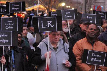 Participants in the Homeless Memorial Day ceremony carry signs bearing the names of 127 homeless and formerly homeless people who died in 2013. (Emma Lee/for NewsWorks)