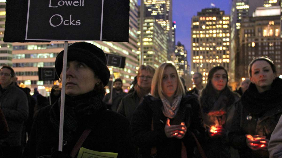 With signs and candles, Philadelphians gather at Thomas Paine Plaza to remember the homeless who died in 2013. (Emma Lee/for NewsWorks)