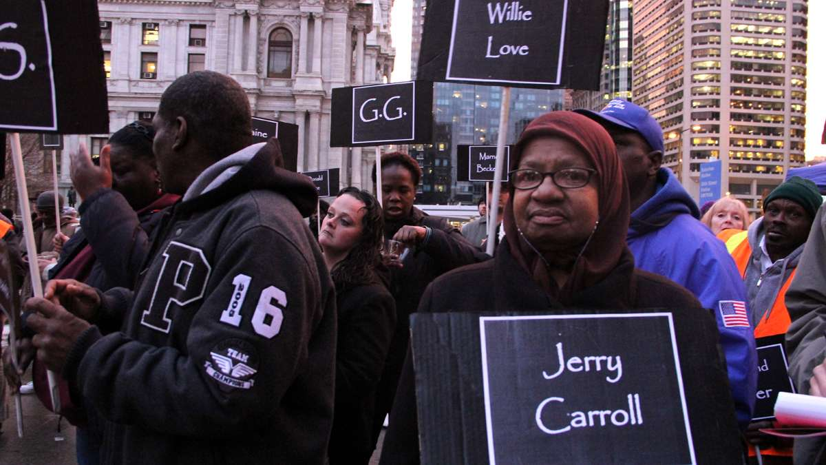 Charlene Wells carries a sign for Jerry Carroll, a man she remembered would ask for change for coffee. She heard he died on the street. (Emma Lee/for NewsWorks)