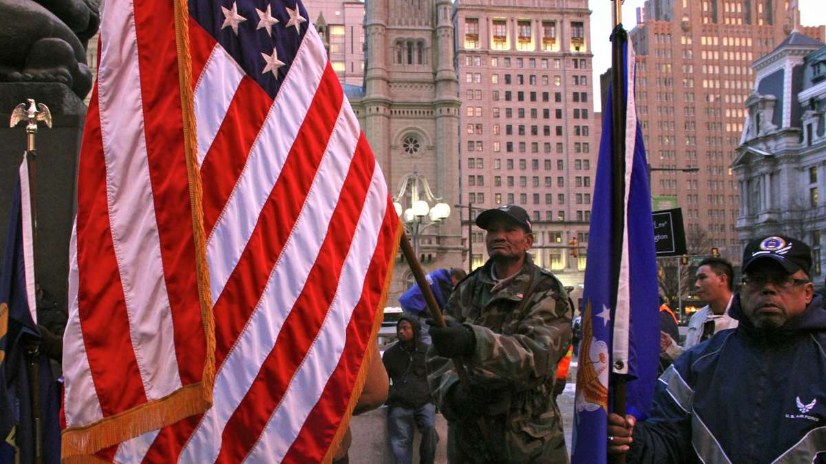 Veteran Eric Taylor, who says he was homeless for four years, carries the flag in honor of the homeless who have died, and his fellow veterans. (Emma Lee/for NewsWorks)