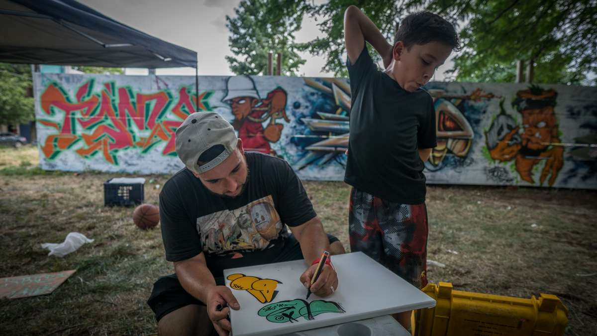 Life Do Grow Farm Art Director Chris Rodriguez works on a drawing while his son Brian looks on