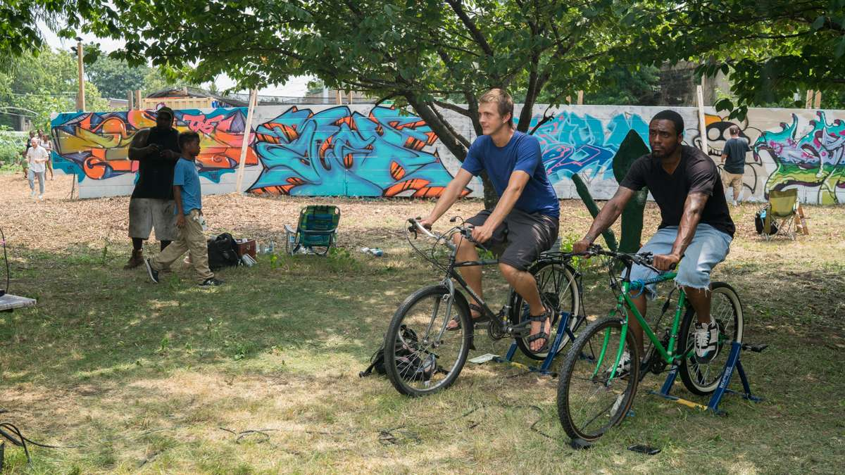 Jesse Phillips (left) and Cool Cceez ride stationary bikes which power a sound system at the 4th annual Hoodstock Festival at Life Do Grow Farm