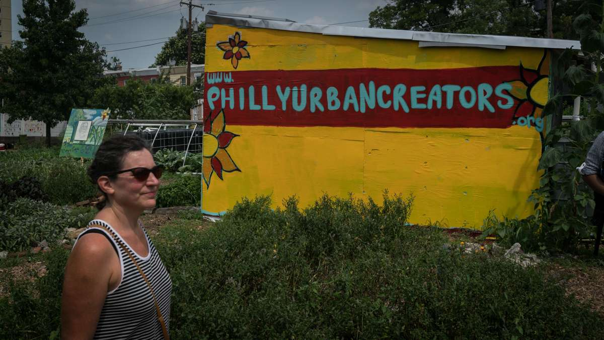 A festival goer passes a structure promoting Philly Urban Creators, the group that hosts the annual Hoodstock Festival in North Philadelphia, July 22, 2017.