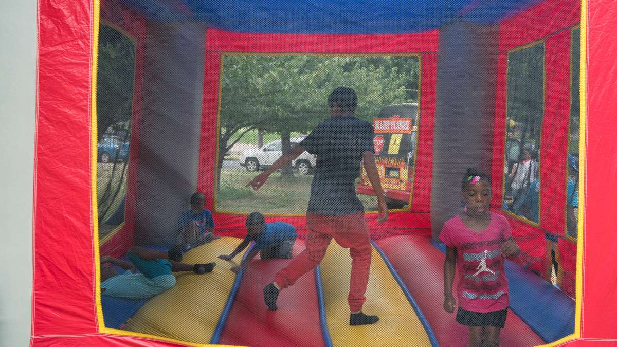 Kids jump in a bounce house
