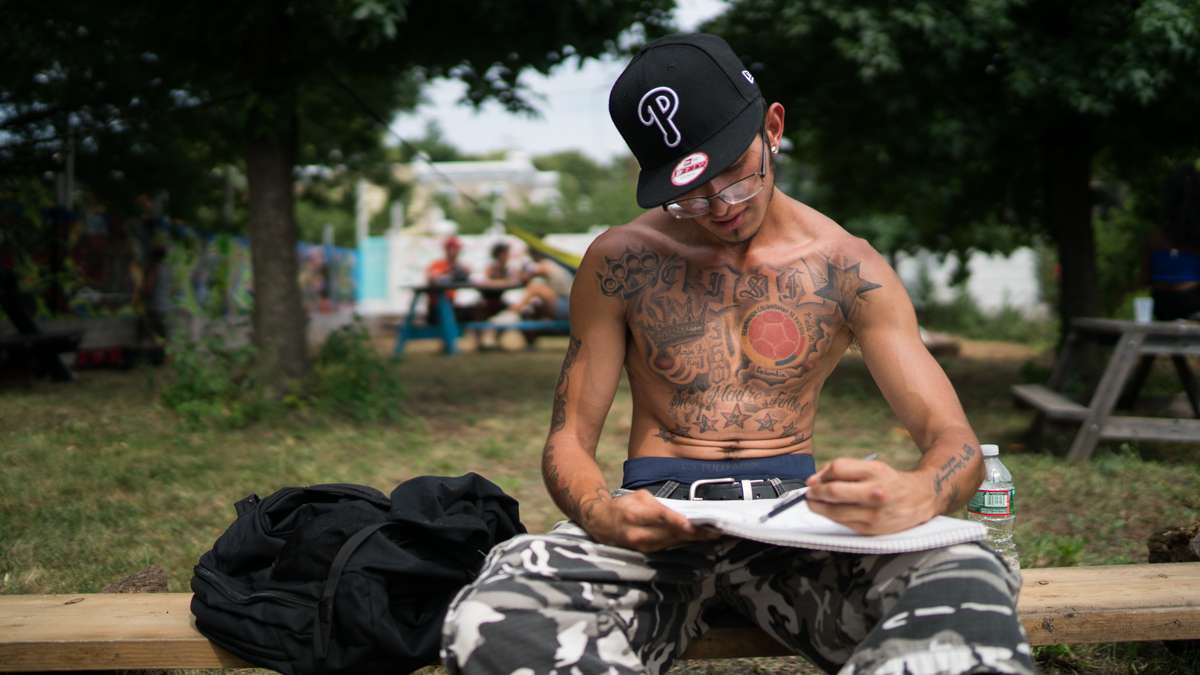 Artist Brayan Leal-Castillo works on a drawing at the 4th annual Hoodstock Festival in North Philadelphia on July 22, 2017.