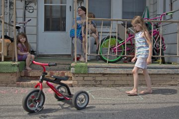 Heather Hoover sits on her porch while her children, Emmalie, 6, Hannah, 3, and Jared, 1, play in front of their home in Mahanoy City, Pennsylvania.  Hoover, a mother of eight, hopes to move to a place with more space for her children to play. She said it seems like the town is falling apart.  (Lindsay Lazarski/WHYY)