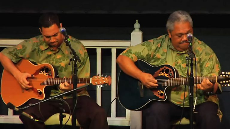 Ikaika Brown (left) performing with his father Kevin Brown (right). (Screen capture from YouTube video)