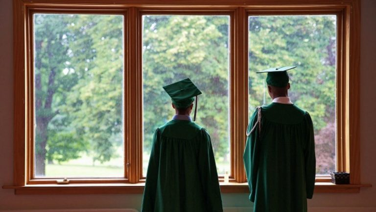 Two members of Germantown's Class of 2012 looked out the windows of New Covenant Church at last year's commencement. This year's ceremony will take on an aura of finality as the school will close on Friday. (Bas Slabbers/for NewsWorks)