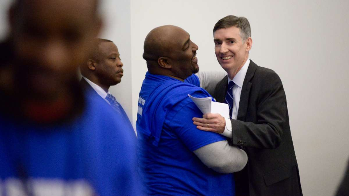 William Jackson embraces Mark Gleason, the executive director of the Philadelphia School Partnership. PSP had promised a $1.5 million grant to Wister if Mastery was given control.  (Bastiaan Slabbers for WHYY)