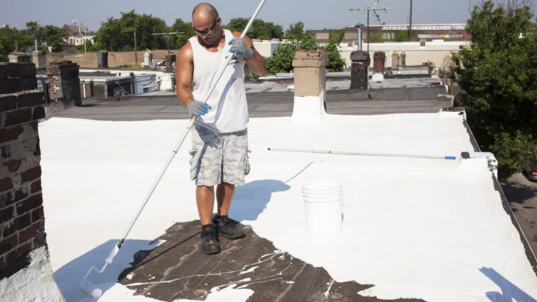 Roofer Rob Nolfi applies a reflective topping on a rehabbed roof in North Philadelphia. Cool roofs help keep temperatures down when the city heats up. (Irina Zhorov/The Pulse)