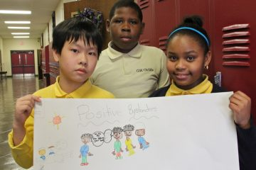 As part of CHOP's anti-bullying program, Childs Elementary fourth-graders (from left) Tuong Truong, Jabree Coleman and Sydney Hall made posters to show what they've learned. (Emma Lee/for NewsWorks)