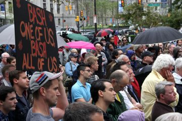 Standing in the rain, the somber crowd listens to a series of speakers, many of whom urged hate crime legislation that would include attacks motivated by sexual orientation. (Emma Lee/WHYY)
