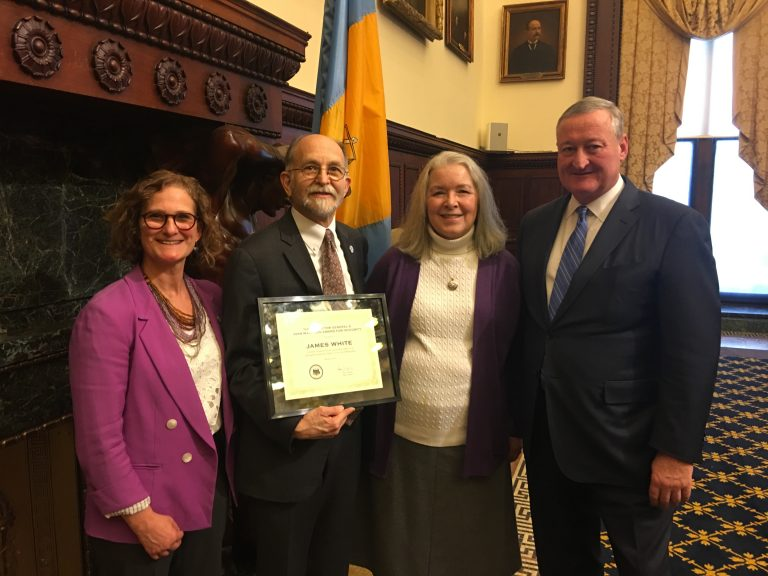Jim White (center) receives the 2017 Joan Markman Award for Integrity flanked by his wife, Clare Bohn, Mayor Jim Kenney and Inspector General Amy Kurland (left). (Tom MacDonald/WHYY)