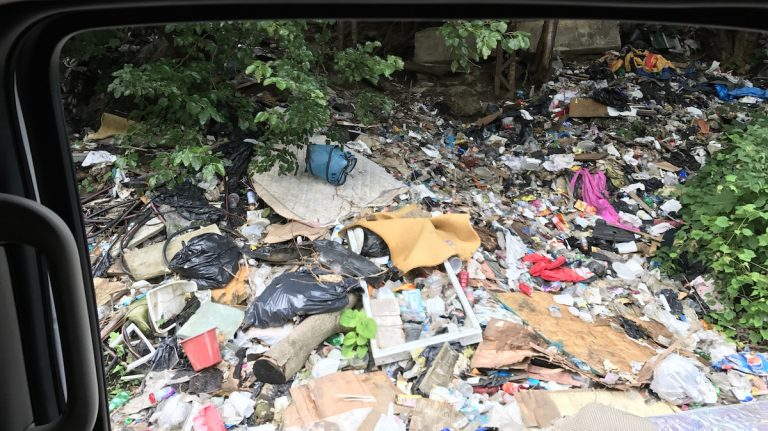 Trash near a heroin encampment is seen from a Conrail vehicle on Thursday. (Joel Wolfram / WHYY)