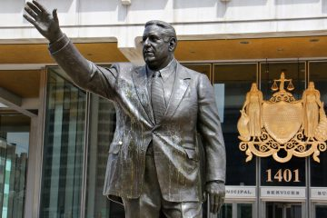 The statue of former Philadelphia Mayor Frank Rizzo drips with egg  Wednesday. The statue is increasingly the target of vandals and protesters who see it as a symbol of racism. (Emma Lee/WHYY)