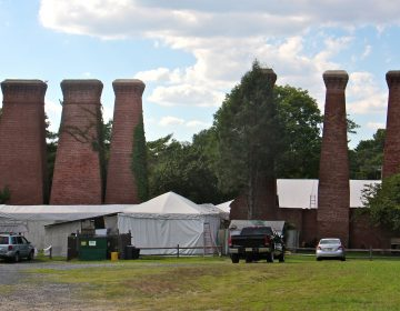 The smokestacks of the former Lucas paint factory loom over the Sherwin-Williams/Hilliards Creek Superfund site in Gibbsboro, New Jersey. Contamination at the site stems from improper paint disposal by Lucas Paint Works and its successor, Sherwin Williams Inc. (Emma Lee/WHYY)