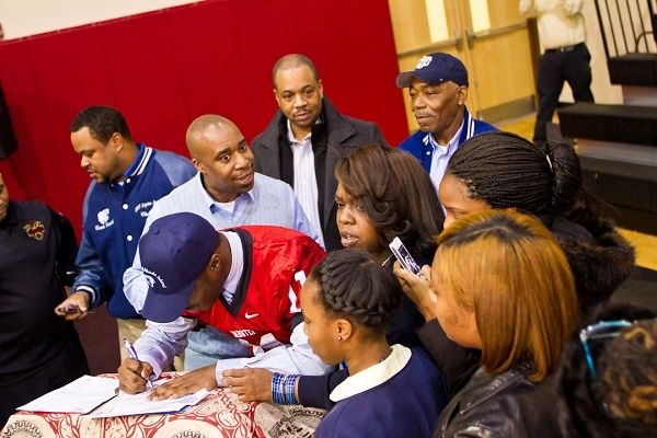 <p><p>Eerin Young was surrounded by family members while he signed on the University of Rhode Island's dotted line. (Brad Larrison/for NewsWorks)</p></p>