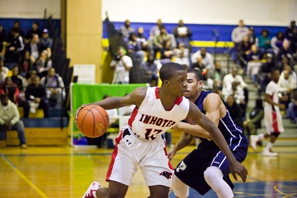 Imhotep Guard Jakwan Jones gets past Steve Griffin of Philadelphia Electrical and Technology Charter School to help lead Imhotep to a 51-43 win in the Public League playoffs Saturday. (Brad Larrison/for NewsWorks)