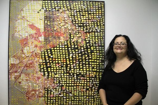 """<p><p>Featured artist Susan Mangan stands beside her piece """"Tide"""" at the Imperfect Gallery show last weekend. (Trenae V. McDuffie/for NewsWorks)</p></p>"""