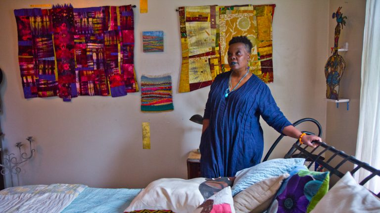 Vashti DuBois stands over her bed. (Kimberly Paynter/WHYY)