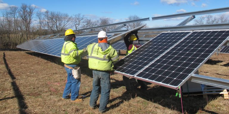 Workers install solar panels at  Delaware Valley Regional High School in Frenchtown, New Jersey. (Phil Gregory/WHYY)