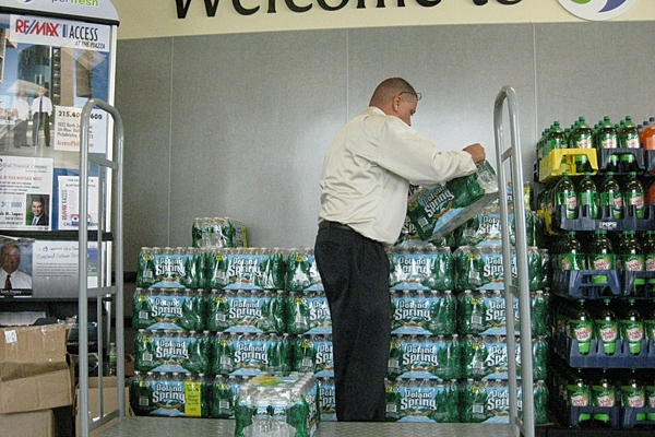 A Superfresh employee replenishes depleted stocks of bottled water at a store in the Northern Liberties. (Peter Crimmins/For NewsWorks)