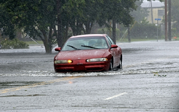 A man drives his car through a flooded street in New Bern, N.C. With flooding likely here, area motorists have been warned to never drive into standing water. (AP Photo/Chuck Burton)