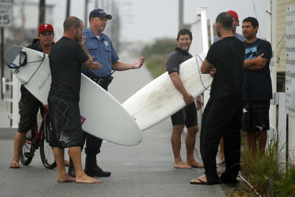 A Cape May police officer, second from left, talks with a group of surfers on the boardwalk early Saturday, Aug. 27, 2011, in Cape May, N.J. (AP Photo/Mel Evans)
