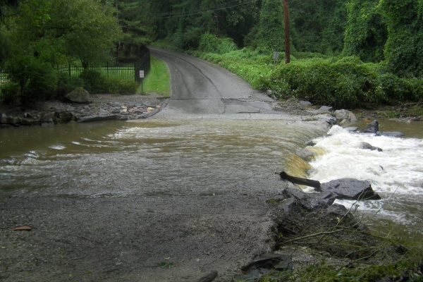 Mill Creek spills over Righters Mill Road Sunday in Gladwyne. (Jennifer Lynn/For NewsWorks)