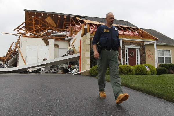 A member of the Delaware State Police walks away from a house that was heavily damaged by a possible tornado in Lewes, Del., Sunday, Aug. 28, 2011, after Hurricane Irene churned along the Delaware coast overnight. (AP Photo/Patrick Semansky)