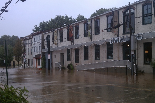 Flooding could be seen in Manayunk Sunday in front of this building at the intersection of Shurs and Main Street. (Megan Pinto/For NewsWorks)