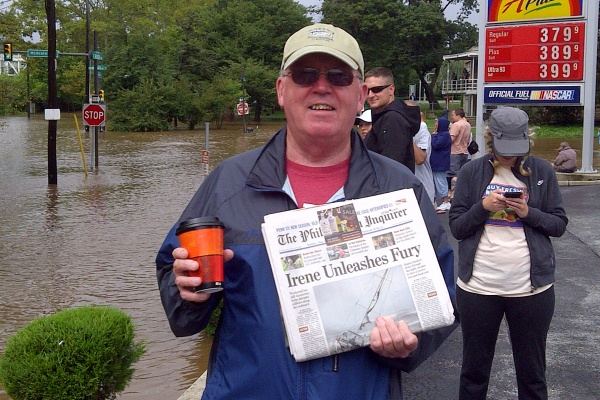 Sam Malloy, of East Falls, holds up a newspaper about Hurricane Irene. (Brian Hickey/For NewsWorks)