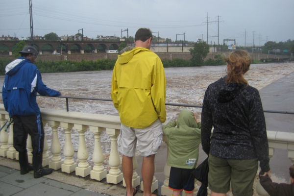 A few people stop to take a look at the water levels from the pier at Fairmount Water Works. (Maiken Scott/For NewsWorks)