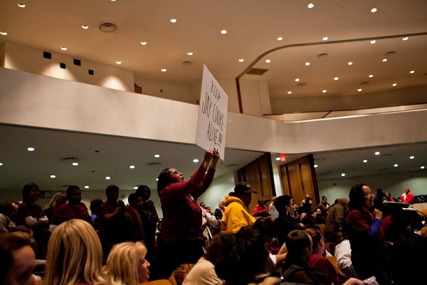 <p><p>Leiya Bullock holds up a sign showing support for Cooke Elementary later in the meeting. (Brad Larrison/for NewsWorks)</p></p>