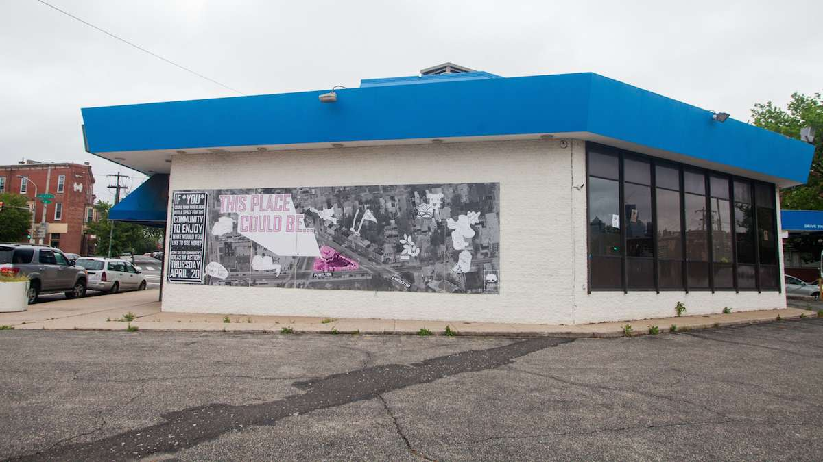 A shuttered United Bank near 38th and Lancaster Avenue is in the process in being converted into a community space. A poster for a meeting on the use of the lot and building is plastered to the wall. (Brad Larrison for NewsWorks)