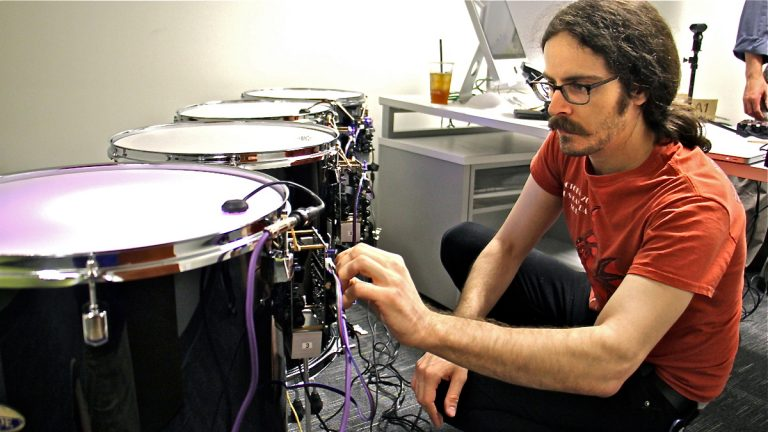 Drexel graduate student Jeff Gregorio connects an array of drums that are sounded by electromagnets. (Emma Lee/WHYY)