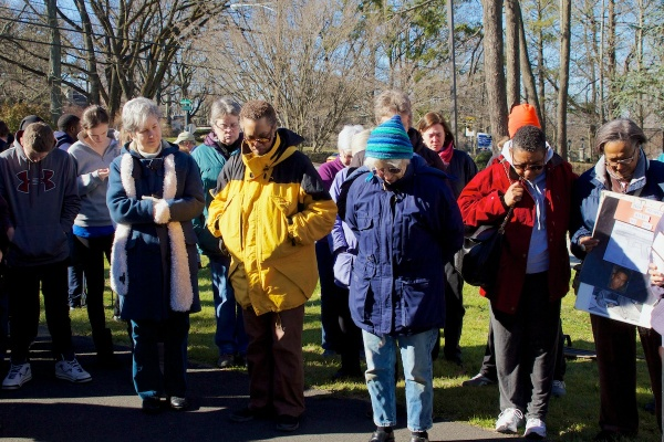 <p>Volunteers bow their heads in a prayer for the victims. ( Jana Shea /for NewsWorks )</p>