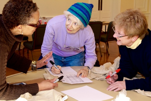 <p>With so many names to write, volunteers coordinate how best to ensure each victim is honored.  ( Jana Shea /for NewsWorks )</p>